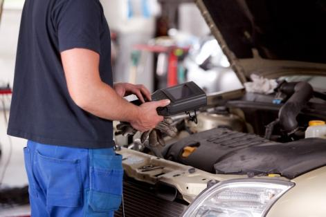 Mécanicien réalisant la révision d'une voiture