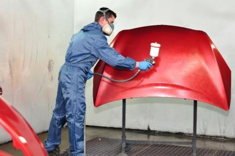 Carrossier rénovant la peinture d'une carrosserie